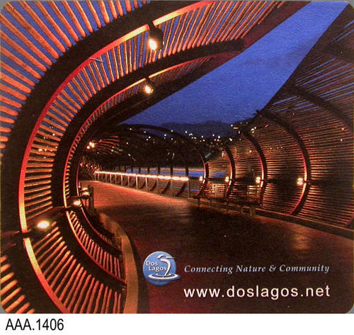 "Thisartifact is a rubber mousepad.  It features a picture of the covered walkway at Dos Lagos along with the Dos Lagos logo.  Text on the mousepad reads:  ""Connecting Nature and Community"" - www.doslagos.net.  This artifact measures:  7 1/2"" x 8 3/8"" x 1/8"""