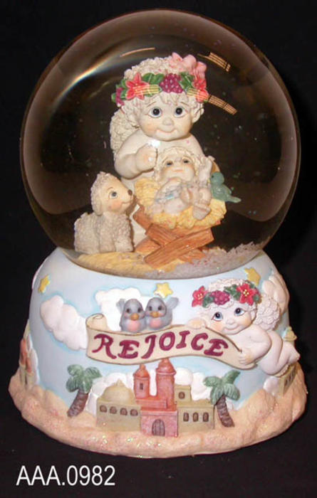 "This artifact is a ""Rejoice"" -  #11917 - snow globe/music box.  The globe features a cherub, a cherub in a manger and a lamb.  Shaking the globe fills the globe with snow. The music box plays, ""Oh Little Town of Bethlehem.""  ""Rejoice"" is from the Dreamsicles line and was made in China.  This artifact measures 5 1/2"" x 4 1/2""."