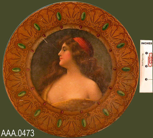 "This artifact is a metal plate with the side profile of a woman in the center.The outer edge of the plate is ornate with gold coloring and rhinestones.  On the back of the plate is written:  ""Compliments of Frank Geith, Corona's Grocer, Corona, Calif."" Donor's Remarks:  This plate was given to Naomi in the early 40's by Mrs. Minnie Ashcroft."