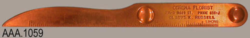 "This artifact is a copper colored, metal letter opener.  The ruler on one edge of the letter opener measures to six inches.  The text on the opener reads:  ""Corona Florist - 705-A Main St. Phone 631-J - Gladys K. Russell.""  This letter opener is from the site of the Sunkist Growers, Inc."
