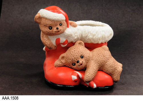 "This artifact is a cast art Santa Claus boot in red with white trim at the top of the boots.  One small, brown bear is lying on the toe of the boot holding a candy cane and the other bear is near the top of the boot.  MEASUREMENTS"" H. 4"", W. 4"", Depth. 4"".  CONDITION:  Very good."