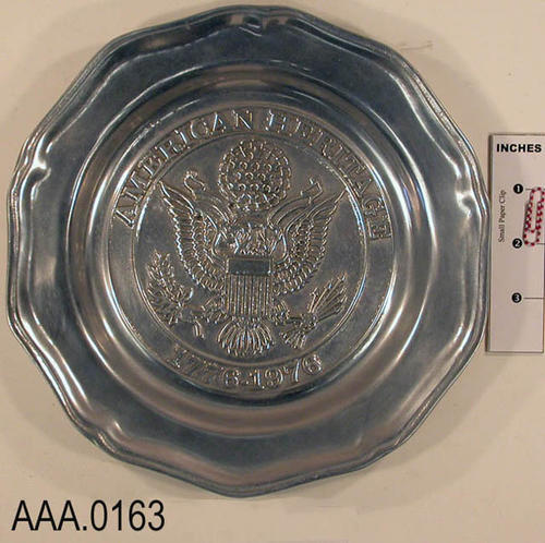 This artifact is an American Heritage Pewter Plate. It is inscribed with the dates 1776-1976.  The back of the plate is inscribed:  Limited Edition, Our nation 1776-1976.  Sunkist 1893-1976.  This plate is from the Cantrell Collection.