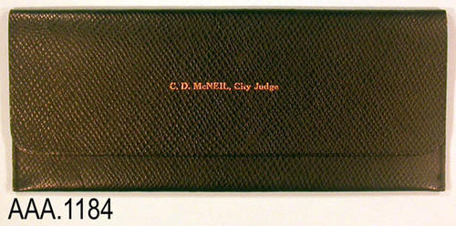 "This artifact is a leather check holder.  Text on the outside cover reads:  ""C. D. McNeil, City Judge.""  The text inside the holder reads: ""Citizens Bank - Corona, Calif."" This check holder measures 10"" x 4 1/8""."