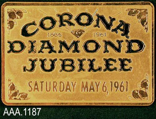 "This artifact is a plaque with the following text:  ""Corona - 1886 (image of a diamond) 1961 - Diamond - Jubilee - Saturday, May 6, 1961."" This plaque measures 2 7/8"" x 2""."