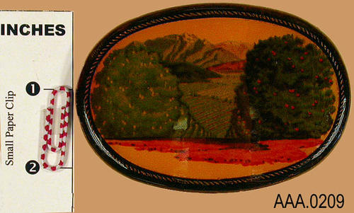This artifact is a belt buckle.  It has a scene of an orange grove looking toward the mountains.  The buckle is in a plastic case.