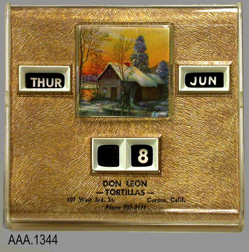 "This artifact is a square, plastic calendar.  The face of the calendar is gold showing through the clear plastic.  This calendar shows the day, month and date.  The calendar information is changed by turning plastic knobs on the back. At the top of the calendar is a small winter scene with a snow covered house.  Black text at the bottom of the calendar reads:  "" Don Leon - Tortillas - 107 West 3rd St. - Corona, Calif. - Phone 737-2171.""  This calendar measures 4 3/8"" square.  The calendar comes in a mustard colored box."