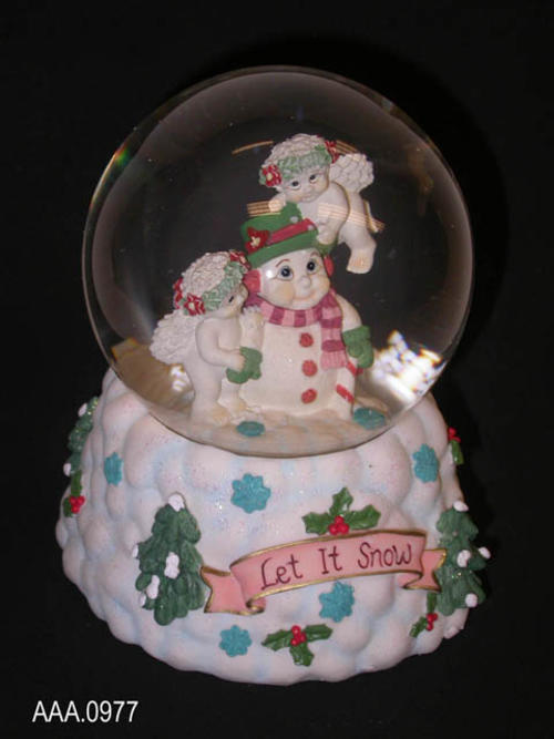 "This artifact is a ""Let It Snow"" -  #11918 - snow globe/music box.  The globe features a snowman with two cherubs.  Shaking the globe fills the globe with snow. The music box plays, ""Frosty The Snowman.""  ""Let It Snow"" is from the Dreamsicles line and was made in China.  This artifact measures 5 1/2"" x 4 1/2""."