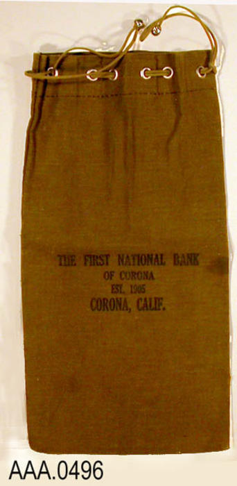 "This artifact is a cloth, money deposit bag.  The following text is printed on the bag:  ""Deposit With First National Bank - Corona, Calif."""