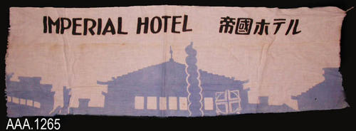 "This artifact is a piece of  white material, the exact use of which is unknown.  In light blue across the bottom is an outline of a building and the following black text is printed on the upper white portion:  ""IMPERIAL HOTEL.  This is followed by five oriental characters.""  This piece of cloth measures 38"" (L) and 11 3/4"" (W).  CONDITION:  The ends of this piece of material are frayed."