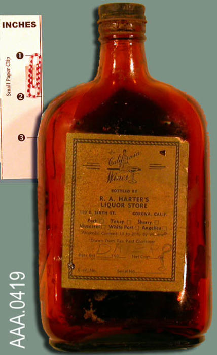 "This artifact is a brown glass bottle with a black screw top.  One pint in size.  There is the following writing on the bottle:  ""California Wines - Bottled by R. A. Harter's Liquor Store - 110 E. 6th Street, Corona, California."