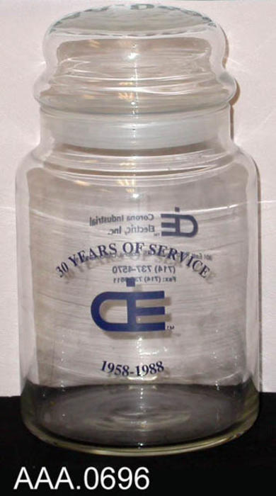 "This artifact is a glass canister with lid.  The front is imprinted with blue text: ""30 YEARS OF SERVICE, CiE [logo], 1958-1988.""  The back is imprinted with blue text with logo, address, phone and fax."