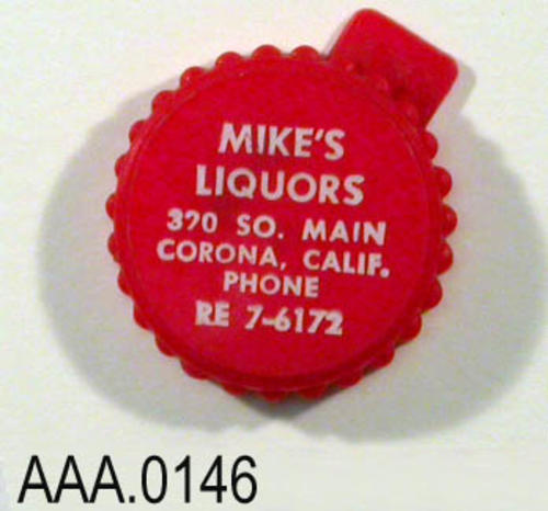 "This artifact is a red bottle cap with the following text imprinted in white letters:  ""Mike's Liquors - 370 S. Main -Corona, California - Phone:  RE 7-6172."""