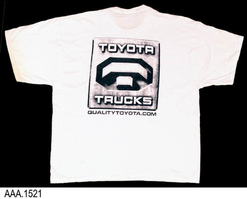 This artifact is a white, 100% cotton, T-shirt in adult size 2XL.  On the front of the T-Shirt is a small octagon graphic in dark blue with the following text below it:  QUALITYTOYOTA.COM.  On the back is a large square graphic with the text:  TOYOTA TRUCKS, and below the graphic: QUALITYTOYOTA.COM. The photograph shows only the back graphic.  QUANTITY:  2.