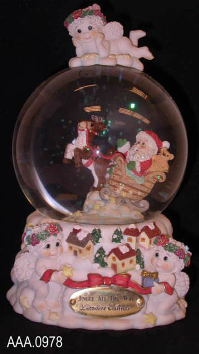 "This artifact is a ""Jingle All the Way"" -  #11921 - snow globe/music box. On top of the globe is a resting cherub. Inside the globe is Santa in his sled being pulled by one reindeer  Shaking the globe fills the globe with snow and metalic flecks of green and blue. The music box plays, ""Jingle All the Way.""  ""Jingle All the Way"" is from the Dreamsicles line and was made in China.  This artifact measures 8"" x 4 1/2""."