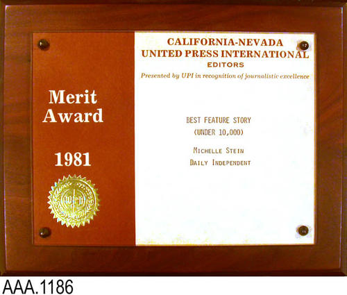 "This artifact is a plaque presented by UPI to Michelle Stein of the Daily Independent for the best feature story under 10,000 words.  The text reads: ""California-Nevada - United Press International - Editors - Presented by UPI in recognition of journalistic excellence.""  Above the gold seal on the left side of the plaque is the following text: ""Merit Award - 1981."" This plaque measures: 10"" x 8""."