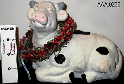 "This artifact is a  piece of cast art.  ""Dairy Delight,"" is a sitting cow with a wreath - #5181/DA381.  CONDITION:  This artifact is in excellent condition."