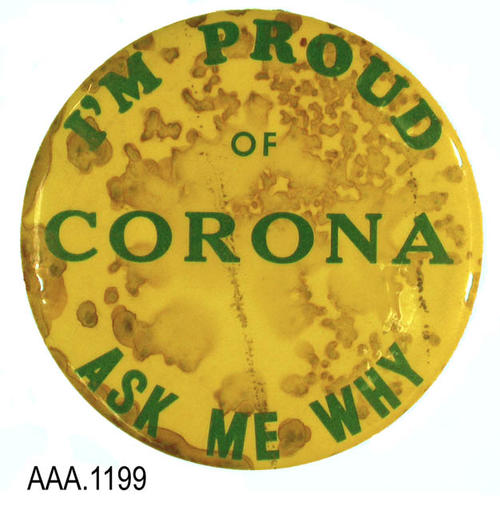 "This artifact is a button with green text on a yellow background.  The text reads:  I'M PROUD - OF - CORONA - ASK ME WHY.""  C. 1965.  This button is 3 1/2"" in diameter.  CONDITION:  Extensive rust marks are coming through the yellow background paper."