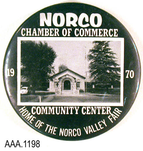 "This artifact is a button from the Norco Chamber of Commerce.  This 3 1/2"" diameter button has white text on a blue background.  The text reads:  ""Norco - Chamber of Commerce - 19 --then a photo-- 70 - Community Center - Home Norco Valley Fair."""