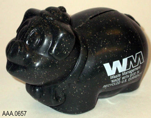 "This artifact is a dark speckled, green piggy bank with WM on the side.  Under the WM is the text, ""Waste Management - Made with $100 in recycled U.S. currency.""  This pggy bank measures 6"" x 3"" x 4""."
