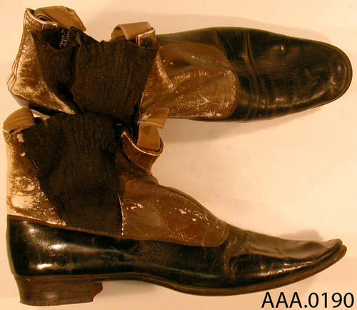 This artifact is a pair of shoes of black leather, flat healed, with elastic side panels.  This pair of shoes is for a very narrow foot and with flat heals suggest they are a child's shoe--possibley a size 9.  CONDTION:  The tops of these shoes are begining to deteriorate.