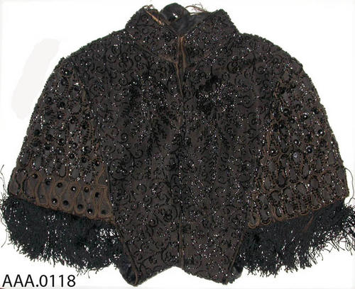 This artifact is a small black jacket with black beads and black fringe.