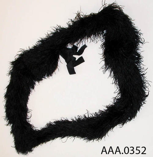 This artifact is a black boa, which is a fluffy scarf.