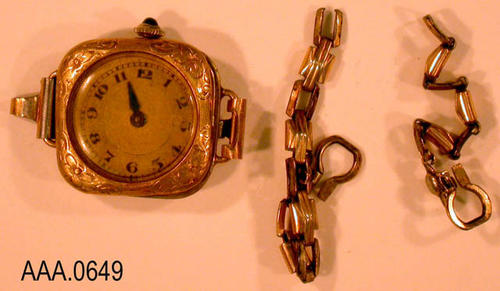 This artifact is a ladies, gold colored watch.  CONDITION: Bad shape:  The crystal comes off, one hand is missing, and the chain is broken.