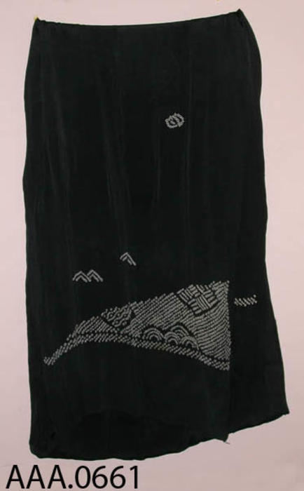 This artifact is a black, ladies shawl, with white stampings in the shape of small white rectangles on each end.  CONDITION:  Has several small holes in the middle of the shawl.