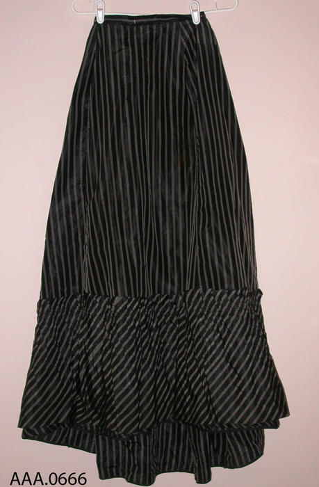 This artifact is a long, black, taffeta skirt with white pinstripes in groups of three.  Circa 1870's-1910.  CONDITION:  Good