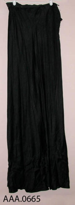 This artifact is a long, black, ladies petticoat.  Circa 1870's -1910.
