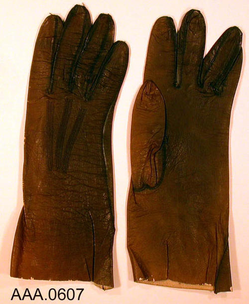 This artifact is a pair of dark brown, real kid, Belgium made, leather gloves in women's size 7 1/2.  CONDITION:  The gloves are well worn, but in good condition.