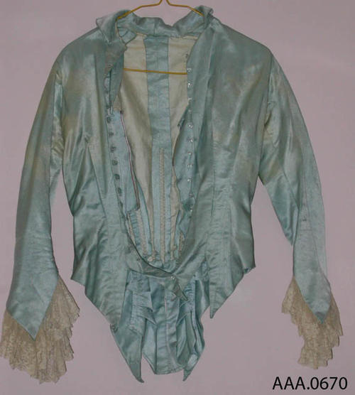 This artifact is a blue-green, ponge (silk thread material), ladies jacket with intricate French lace on the sleeves.  Circa 1870's-1910.  CONDITION:  The material is faded in spots and the lace has yellowed.