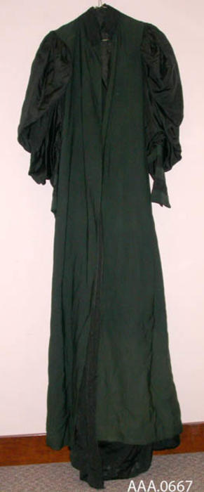 This artifact is a long, dark green, cotton dress with long, black, puma clotton sleeves.  Circa 1870's-1910.  CONDITION:  Fair.