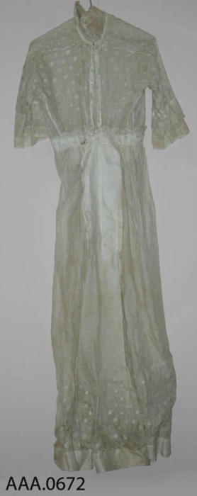 This artifact is a long, off-white, silk organze dress with hand embossed, light green, polka-dots.  Circa 1870's-1910.  CONDITION:  There is a hole near the neck on the front of the dress.