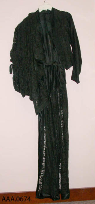 This artifact is a long, black lace, ladies dress with matching shawl.  Circa 1870's-1910.  CONDITION:  Good.  The matching blouse to this artifact is artifact AAA.0675.