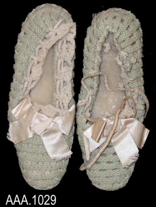 This artifact is a pair of crocheted baby shoes, light green with white ribbon on top.