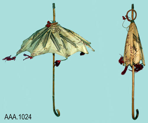 This artifact is a small parasol with a wooden shaft.  The top is cream color with a brown, bamboo like deisgn.  The edge of the parasol is scalloped and has red,cloth tassels.