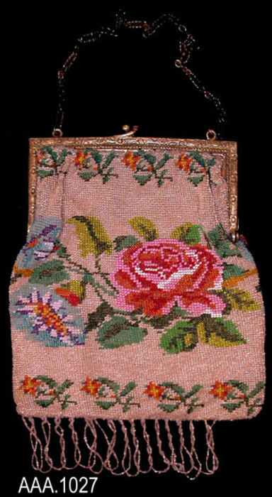 This artifact is a small beaded purse with a red rose and leaf design in the center and an orange colored flower with leaves around the edge.  CONDITION:  This artifact is in good condition.