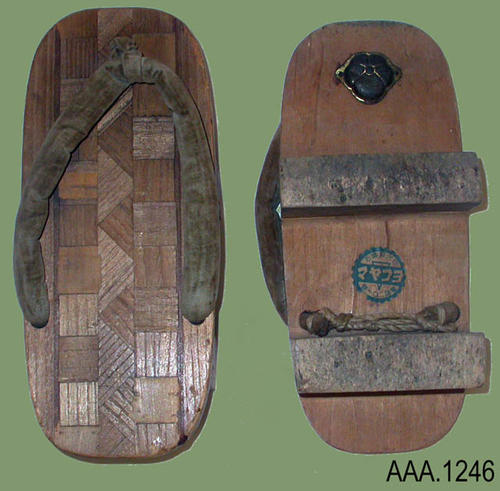 "This artifact is a pair of wooden shoes from Japan.  A cloth strap holds the shoe to the foot.  On the bottom of each shoe at the toe end is a small metal plate with a flower design.  Each shoe measures  8 1/2"" (L), 3 5/8"" (W), 1 7/8' (Thick)."
