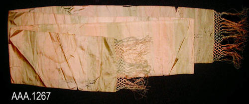 "This artifact is a silk obi.  It measures from fringe end to fringe end 108"" (L) and 7 7/8"" (W).  The fabric is beige and has bands and stripes of pale green and some bands of very pale rose.  The string fringe on each end measures 4 1/2"".  CONDITION:  The fabric is very fragile and is disintegrating.  There are numerous rips in the fabric. Several stains are also visible."