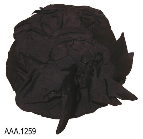 "This artifact is a black hat made from grosgrain material.  It has an open back.  It measures 7 1/2"" (L) and 6"" (W)."