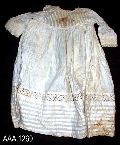 "This artifact is an infant/small child's dress with short sleeves in a cream color.  There are vertical pleats near the neck  and horizontal pleats near the hem.  Above the pleats near the hem is a band of lace. This dress measures 23"" from the neck to the hem.  CONDITION:  The fabric is in generally good condition; however, there are large brown stain areas on both the front and back."