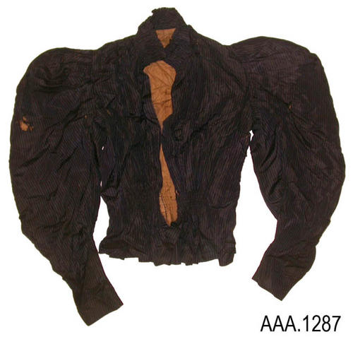 "This artifact is a ladies jacket.  It is dark blue in color with black, vertical, pinstripes.  The linining of the jacket is a dark tan.  This jacket measures 13"" from shoulder seam to shoulder seam.  The length of the jacket is 23 1/2"" measuring from the top of the collar to the bottom of the jacket.  CONDITION:  The fabric of this jacket is disintegrating.  There are numerous holes and places where the fabric is shreading."