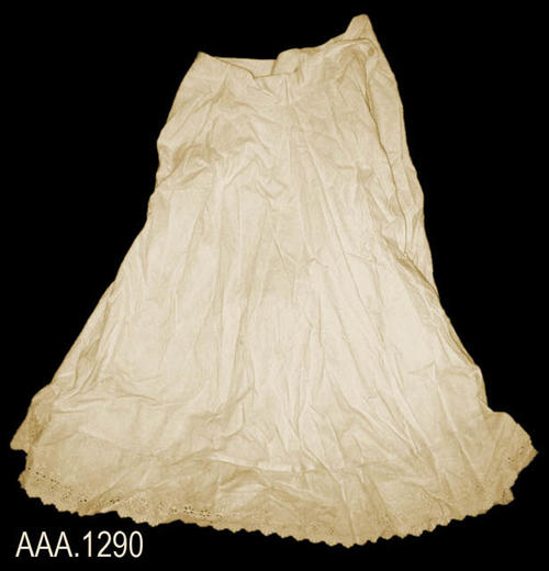 "This artifact is a pair of cream colored pantaloons that resembles a divided skirt.  At the bottom of each leg is a 4 1/2"" band of lace.  The garmet meausres 28"" at the waist and 29 1/2"" in length.  The garmet is in good condition with the exception of a rip in the crotch area."