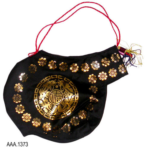 This artifact is part of a Korean costume.  It is irregular in shape and is made with black fabric having a metallic gold flower and geometric design.  A red string handle with multi-colored tassels on one side.
