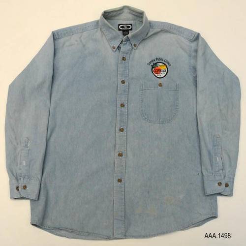 "This artifact is a light blue, denim long sleeved shirt with a button down collar.  Over the left pocket is the City of Corona seal with the words:  ""Corona Public Library"" in a semi-circle above the seal in dark blue stitching."