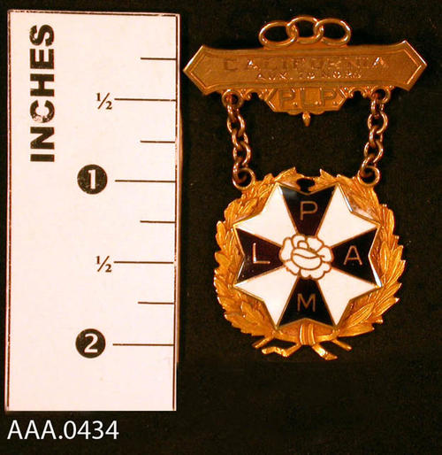 "This artifact is a lapel pin  from the Odd Fellows Lodge and Rebekah Assembly.  This gold medal has three chain links above a bar with the inscription:  ""Calif. Aux. #25.""  Under the bar are the letters, ""P.L.P."", hanging from the bar by two gold chains.  There is a gold circle with an eight pointed black and white inlay star with the letters, ""L.P.A.M."" on the black portion. Donor's Remarks:  This medal was given to Alys Tuthill for an office held in the Rebekah Lodge."
