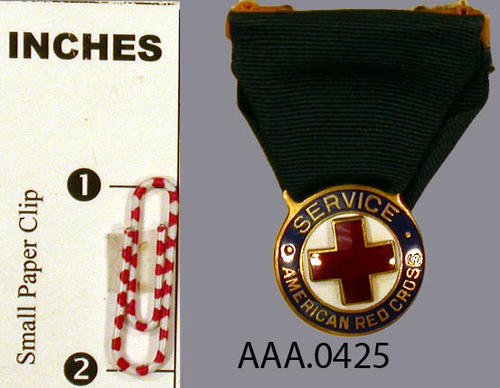 This artifact is a American Red Cross Service Medal. It is made of a brass-like metal base with enameled surfaces of a red cross, white background, and blue background.  A dark blue ribbon attaches the medal to the fastener.
