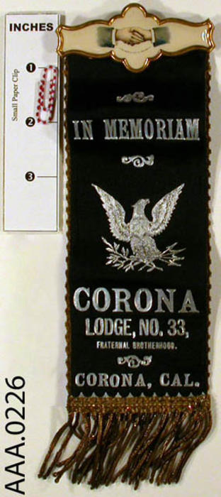 "This artifact is a black ribbon form the Odd Fellows.  The following text appears on the ribbon in silver:  ""In Memoriam - Corona Lodge No. 33, Fraternal Brotherhood Corona, California.""  There is a large silver eagle in the middle.  The clip at the top is two hands shaking on an ivory background, ringed in gold."
