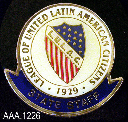 "This artifact is a State Staff pin for the L.U.L.A.C.   The top circular portion of the pin is white with gold text which reads: ""League of United Latin American Citizens - 1929."" In the center of the pendant is a shield with the initials, ""L.U.L.A.C."" going diagonally across the front.  Gold stars on a blue field make up the upper right portion of the shield while red and white stripes the lower left side of the shield.  On a half circular banner below the circular pin, in gold text against a dark blue background are the words:  ""State Staff.""  This artifact measures 1 1/4""."